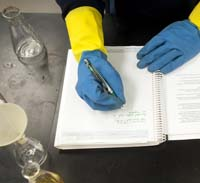 Chemist writes notes during a lab exercise.
