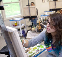 A student paints on an easel.