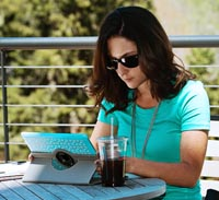 Woman types on a tablet at a cafe table.