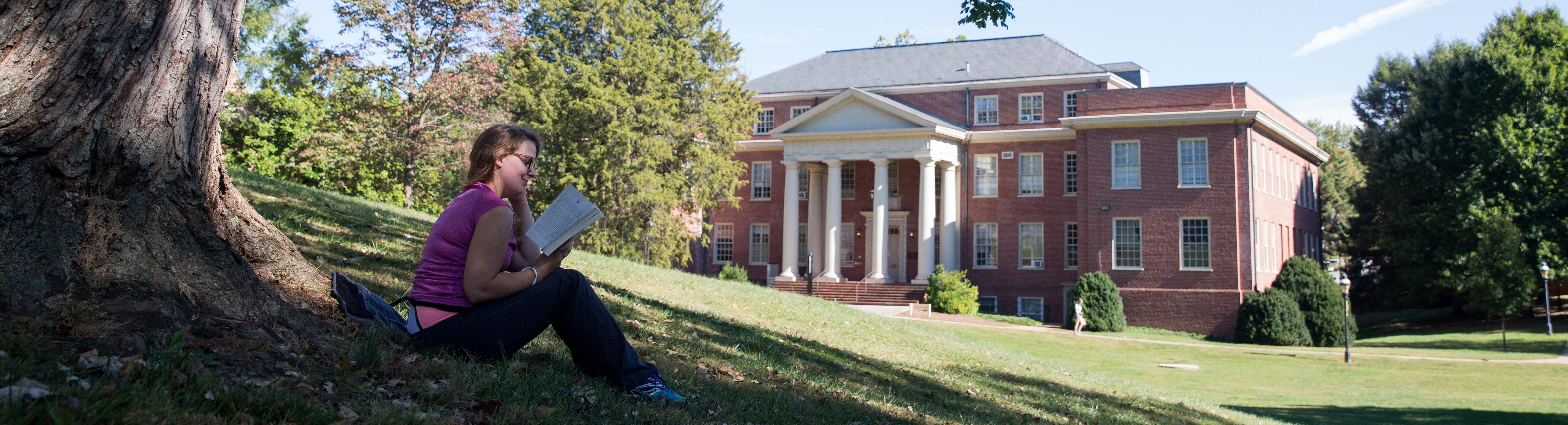 Photo of student reading a book on campus