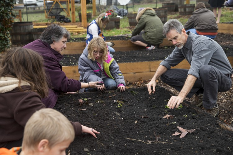 Economics professor John Abell helps local citizens create a community garden at nearby New Vistas School.