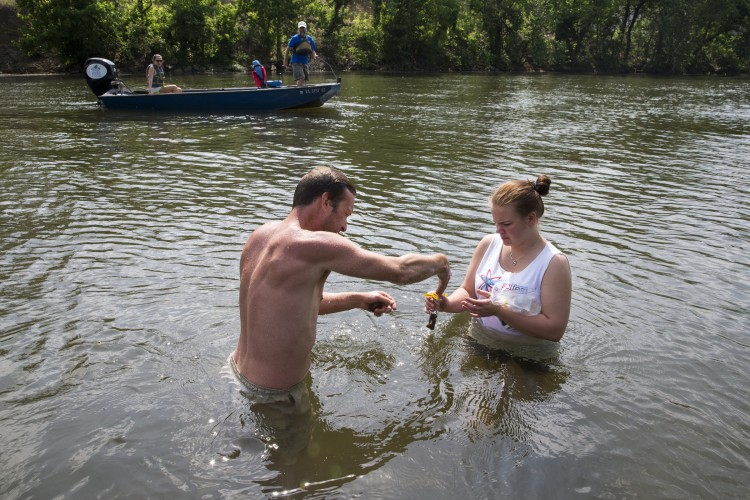 Allison Brooks '18 and Rob Campbell '13 collect soil samples by hand while Melissa Pasierb ''17 and River Keeper Pat Calvert test other sites from a motorboat.