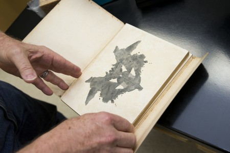 Psychology and environmental studies professor Rick Barnes opens an original printing of a set of Rorschach inkblots from the 1920's.