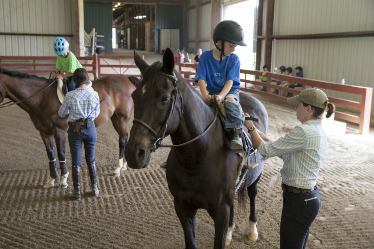 Camp volunteers help children saddle up.