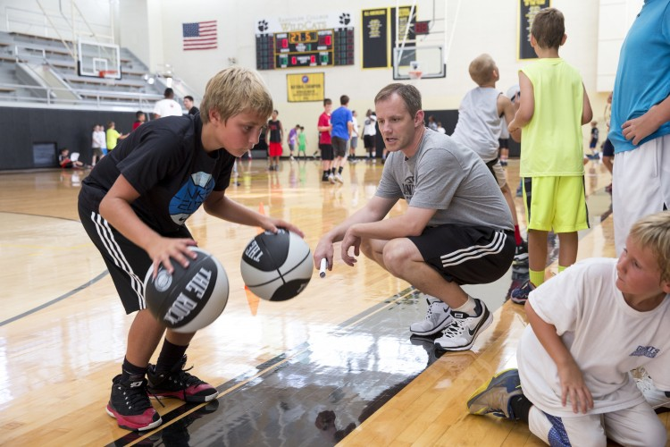 Head men's basketball coach and camp director Clay Nunley talks a camper through a dribbling exercise.