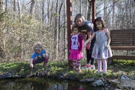 Carrie McCane '16 and RCNS students track the progress of tadpoles living in the pond.
