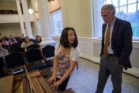 Music professor Emily Yap Chua tests a fortepiano with keynote speaker Nicholas Giordano.