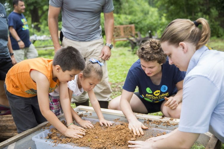Jessy Spencer '18 and sustainability coordinator Sara Woodward '16 filter clay with children at the straw bale workshop in Randolph's Organic Garden last week.