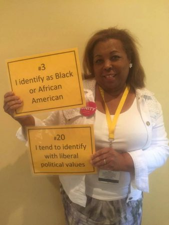 Hermina Hendricks, director of Multi-Cultural Services and instructor in music, holds signs that represent her.