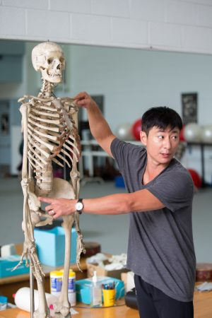 Visiting dance professor Seyong Kim demonstrates how dance motions affect different parts of the human body.