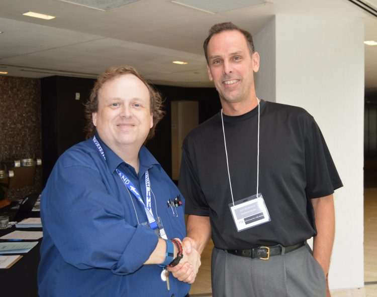 Randolph economics and business professor Jeffery Heinfeldt (right) shakes hands with Timothy Michael, executive director of the Financial Education Association.