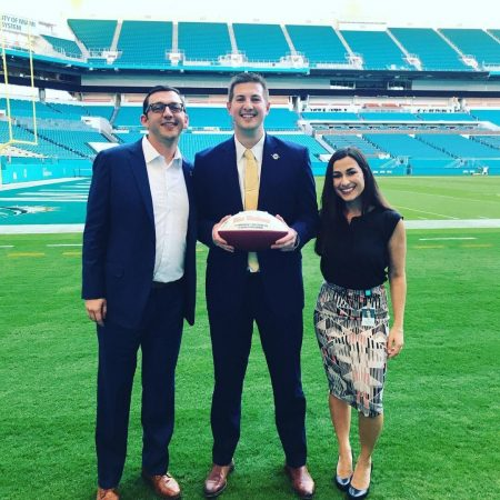 Mitch MacDonald '17 (center) at Hard Rock Stadium, home of the Miami Dolphins. He was  recently promoted to a business development account executive for the organization.