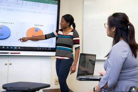Taylor Samuels '18 and mathematics professor Jia Wan compare data about first-year seminar choices.