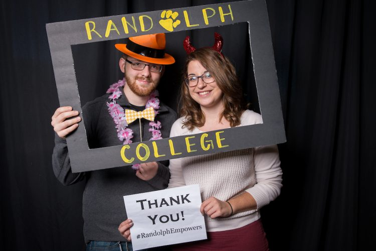 Students pose in the Giving Tuesday photo booth, holding thank you signs.