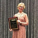 Louisa Branscomb '71 holding her 2017 Distinguished Achievement Award from the International Bluegrass Music Association.