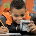A Dearington Elementary School student examines a block from a Curiosity Kit.