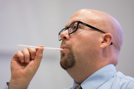 Nicholas Perna leads students on a vocal exercise using straws.