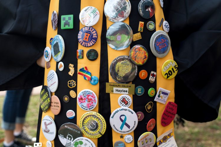 Seniors robes decked out in buttons from various events at the College.