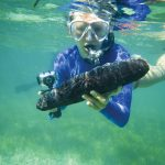 Lydia Edwards '19 examines a specimen during a scuba diving excursion in San Salvador.