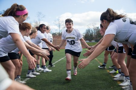 Women's lacrosse teammates form a tunnel and give five to a teammate running through