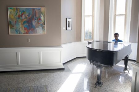 A student plays piano in Main Hall lobby