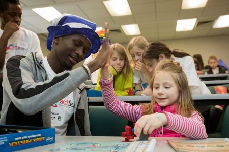 Amadou Beye '19 high fives a young girl at Randolph College's Science Festival
