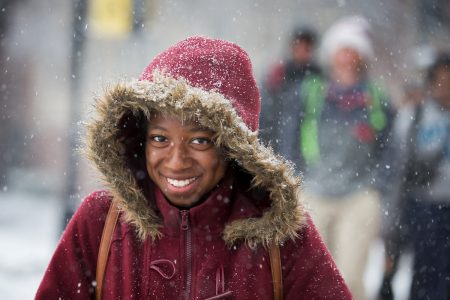 Student wearing a parka with her hood pulled up walks through the snow on front campus
