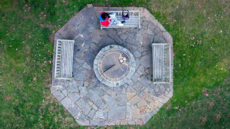 An aerial view, looking straight down at the Sundial and a student sitting on a nearby bench