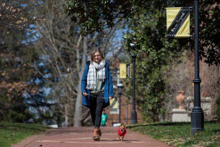 Lydia Edwards '19 walking a dog on front campus