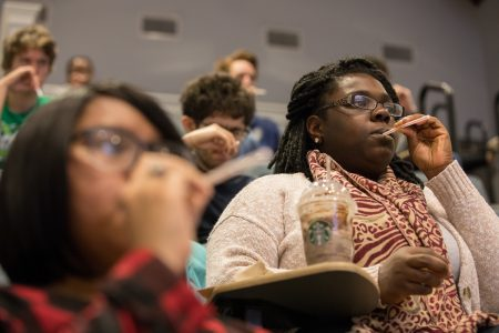 Students hold straws to their mouths in a Science Festival workshop on vocals and acoustics, led by Nicholas Perna.