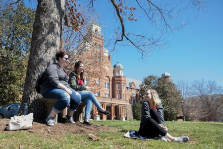 Three female students sitting and hanging out in front of Main Hall