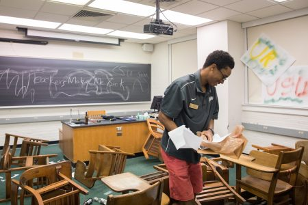 "Josh Yeast '19 prepares the ""Crime Scene Investigation"" activity, which involved a vandalized classroom."