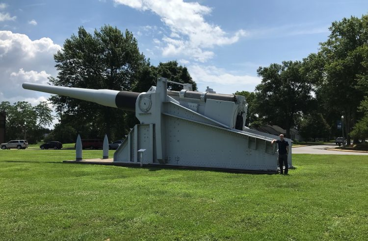 Alex Clem '19 stands next to a cannon used on a ship in WWII.