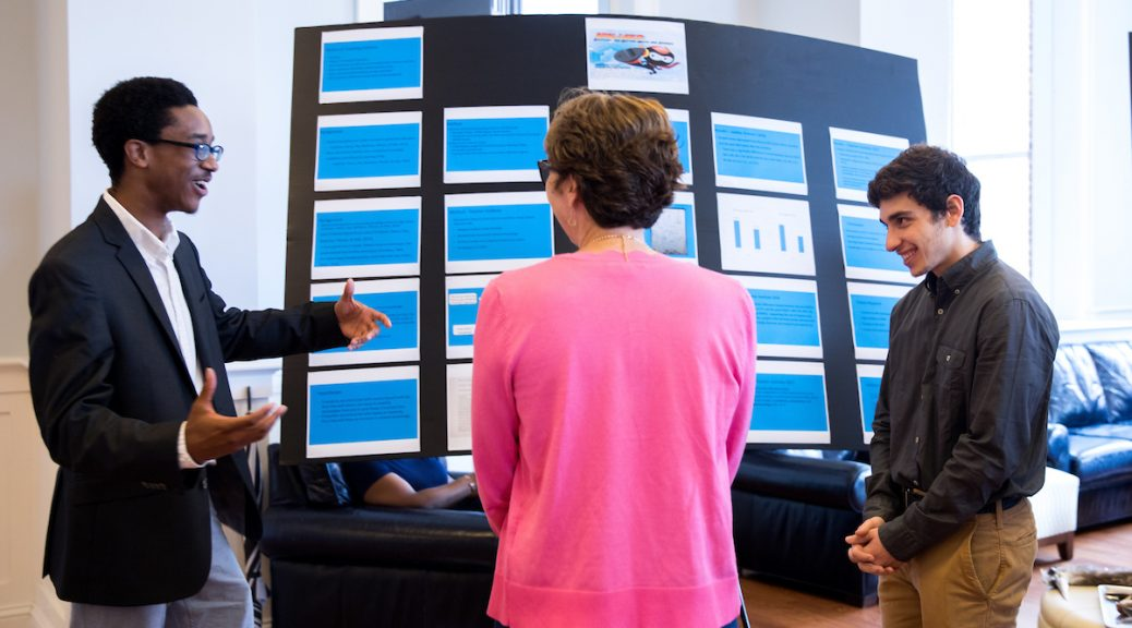 """Josh Yeast '19 (left) and Damien Douglas present a poster about the project, """"Teaching Math and Science in a Changing World."""""""