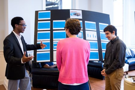 "Josh Yeast '19 (left) and Damien Douglas present a poster about the project, ""Teaching Math and Science in a Changing World."""