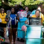 Move-in volunteers and new students push luggage carts along the Red Brick Path