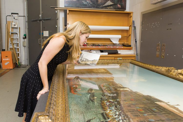 Elisabeth Price '16 examines a painting in the vault