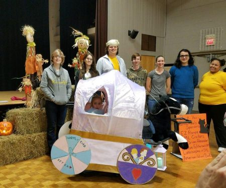 "Randolph students pose with Maddie, age 6, in her Cinderella-themed costume, ""Maddierella"""