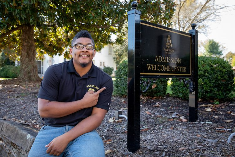 Corey Brown '16 in front of Randolph's Admission Welcome Center