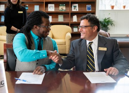 Nick George, founder and executive director of The Listening, and Carl Girelli, vice president for academic affairs and dean of Randolph College, shake hands following the announcement of the new partnership.