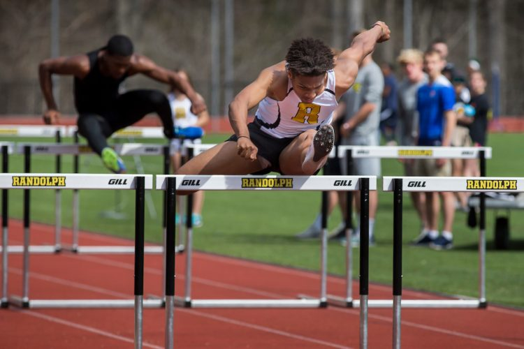 DJ Petty '20 jumps a hurdle at a Randolph track meet in 2018