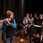 Hailey Gilman plays flute while the rest of the group watches the audio frequency levels