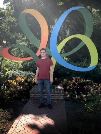 Cody Carpenter in front of a large statue of the Busch Gardens logo