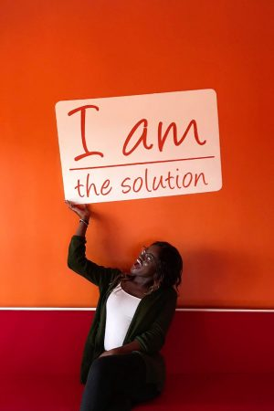 "Ranita Opoku-Sarfo with a sign that reads ""I am the solution"""