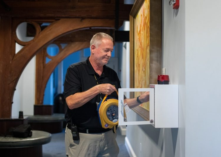Kris Irwin, director of campus safety, installs an automated external defibrillator (AED) in the Student Center