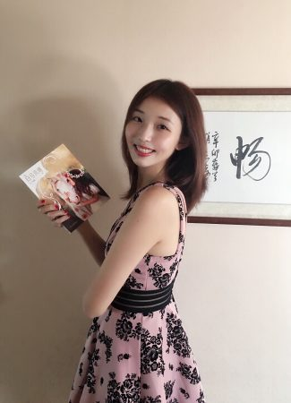 Di Bei holds a copy of her book