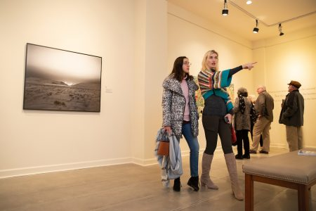 Elisabeth Ayars points to a piece in the exhibition