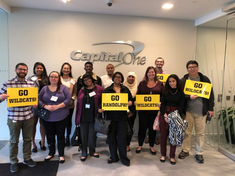 """Students and Capital One staff pose with signs that read, """"Go WildCats!"""""""