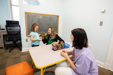 Psychology professor Sara Beck and her daughter work with Cassidy Carter in the new children's research space