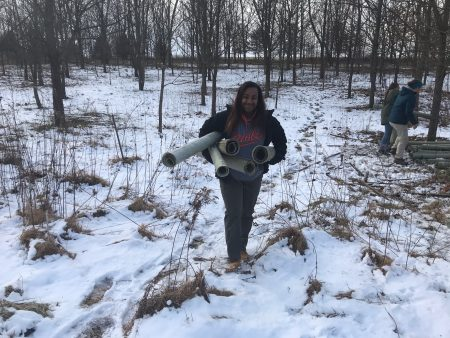Tyrah Cobb-Davis helping load used tree shelters for future reforestation projects.